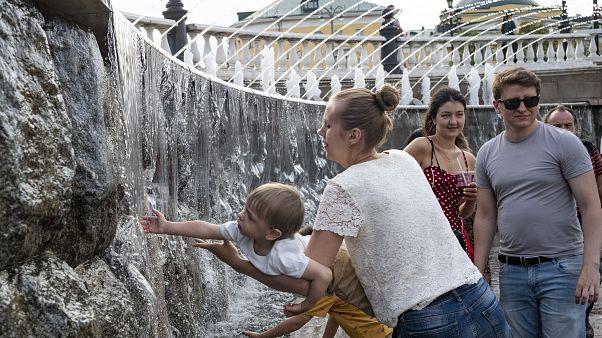 Ребенок играет с фонтаном в центре Москвы.