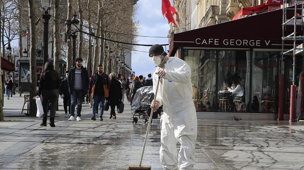 A masked worker wipes the pavement of the Champs Elysees avenue in Paris, Friday, March 13, 2020.