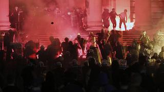 Protesters clash with riot police on the steps of the Serbian parliament during a protest in Belgrade, Serbia, Friday, July 10 2020.