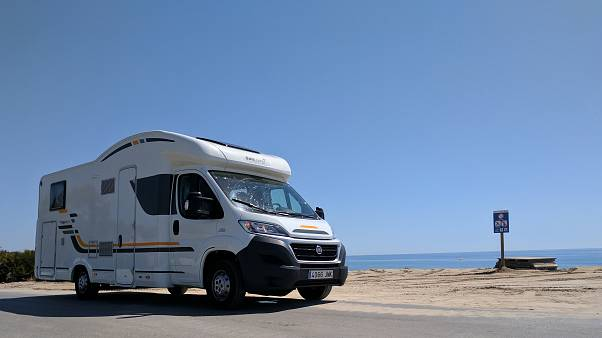 AP Photo/Nicole Evatt - A recreational vehicle parked by the beach in Alcossebre, Spain