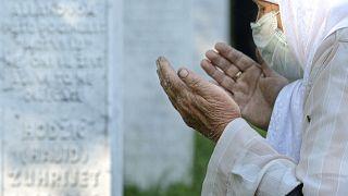 عجوز بوسنية تصلي بالقرب من ضريح في بوتوكاري، ليس بعيداً من سريبرينيتسا