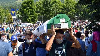 Bosnian Muslim men carry the casket of a newly identified victim during a burial ceremony marking the 25th anniversary of the Srebrenica massacre, Potocari, Bosnia, 11/7/20.