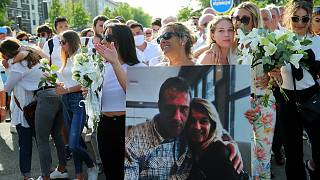 Veronique Monguillot holds a photo of her with her husband during a protest march in Bayonne