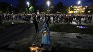 Uma mulher reza durante os protestos de sábado à noite em Belgrado