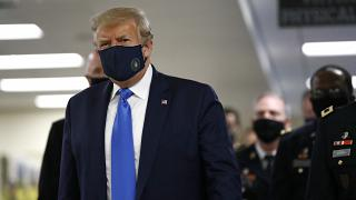President Donald Trump wears a face mask as he walks down a hallway during a visit to Walter Reed National Military Medical Center in Bethesda, Md., Saturday, July 11, 2020.