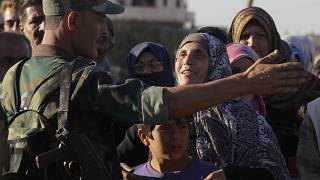 A woman talks with a soldier of the Syrian army during distribution of humanitarian aid from the Russian military in the town of Rastan, Syria, file photo, August 15, 2018.