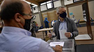 Inigo Urkullo, Basque Lehendakari or Regional President, right, wears a face mask while voting in Basque regional elections.