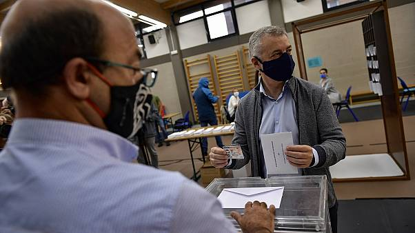 Inigo Urkullo, Basque Lehendakari or Regional President, right, wears a face mask while voting in Basque regional elections.