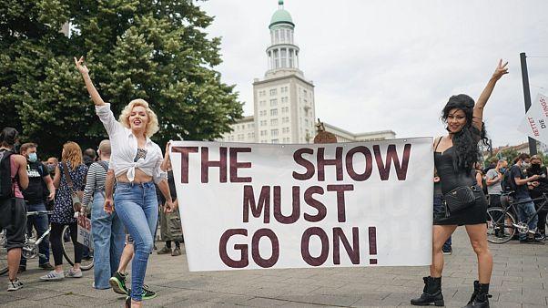 """Berlin'de gösteri dünyasında çalışan insanların koronavirüs uygulamaları protestosunda iki kişi """"Gösteri Devam Etmek Zorunda"""" pankartı taşıyor"""