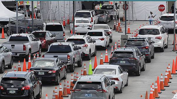 Vehicles wait in line at a drive-thru COVID-19 testing site outside Hard Rock Stadium in Miami Gardens, Florida