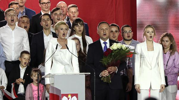 Incumbent President Andrzej Duda, center, his wife Agata Kornhauser-Duda, left, and daughter Kinga, right, sing along with supporters in Pultusk, Poland, Sunday, July 12, 2020