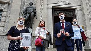 Members of Noi Denunceremo (We will denounce) Facebook group, holds pictures of their relatives, victims of COVID-19, as they stand in front of Bergamo's court.