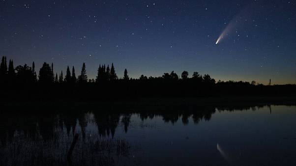 Comet Neowise streaks across the night sky over Wolf Lake in Brimson, Minnesota, USA. July 14, 2020