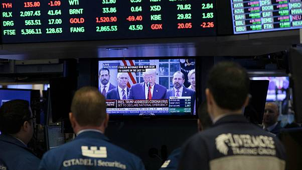 Traders listen at the New York Stock Exchange to President Donald Trump's televised speech from the White House