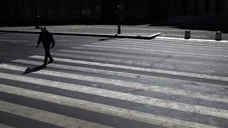 A man crosses an empty street during a nationwide confinement to counter the Covid-19, in Paris, Saturday, April 4, 2020.
