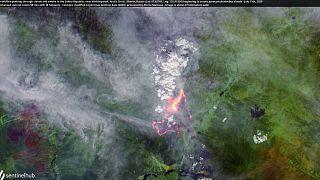 A wildfire peeking through clouds and smoke in the Sakha Republic, near Verkhoyansk, Arctic Circle