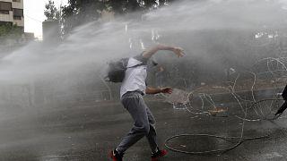 متظاهر لبناني يتعرض للرش بالمياه فيما كان يرمي الحجارة على الشرطة
