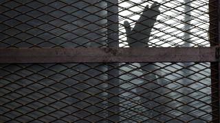 صورة أرشيفية لأحد أعضاء جماعة الإخوان المسلمين خلق القضبان أثناء جلسة محاكمة في عام ٢٠١٥