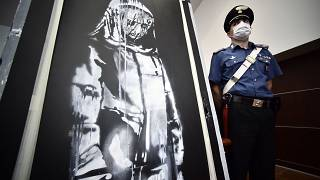 A policeman stands guard near a piece of art attributed to Banksy, that was stolen at the Bataclan in Paris in 2019