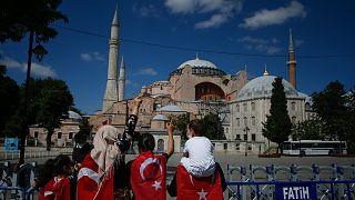 Török zászlóba burkolt emberek az átalakítás miatt bezárt isztambuli látványosság, az Hagia Sophia előtt
