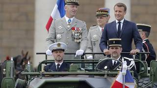 France's President Emmanuel Macron stands in the command car as he reviews troops before the start of the Bastille Day parade. 14 July, 2020.