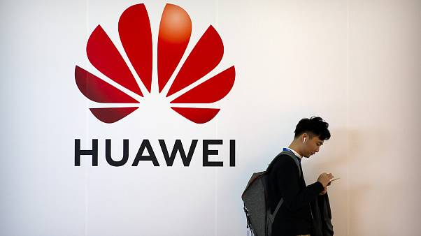 FILE - In this Oct. 31, 2019, file photo, a man uses his smartphone as he stands near a billboard for Chinese technology firm Huawei at the PT Expo in Beijing.