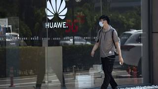 A man wearing a mask to curb the spread of the coronavirus walks past a Huawei store promoting 5G technologies in Beijing on Wednesday, July 15, 2020.