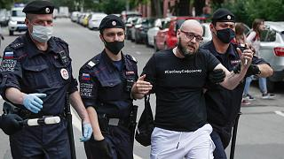 """Police officers detain Kommersant newspaper journalist Alexander Chernykh, who is wearing a T-shirt with sign """"Freedom to Safronov"""", during Monday's rally"""