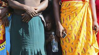 A child pictured in February standing between women waiting to receive food parcels in Zimbabwe, where the UN estimates more than half the population is in need of food assist