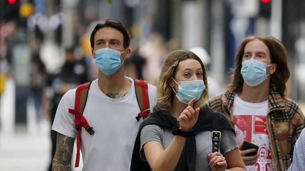 Shoppers wearing protective face masks walk along Oxford Street in London, Tuesday, July 14, 2020.