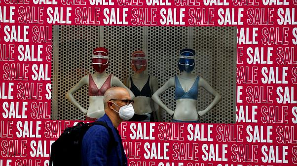 A man wearing a protective face mask walks past a shop window in London