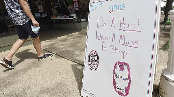 A shopper walks past a sign advising mask usage in downtown St. Joseph, Michigan, US.