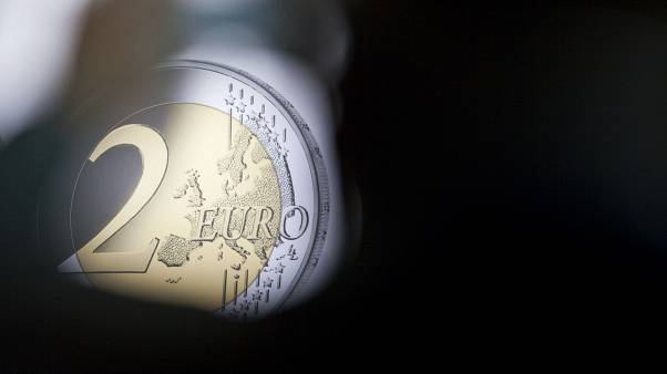 A man takes a photograph of a banner showing a two Euro coin during the presentation of a special edition of the coin at the chancellery in Berlin, Germany, Thursday, Feb. 9,