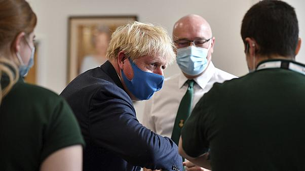 British prime minister Boris Johnson wears a mask while visiting the HQ of the London Ambulance Service.