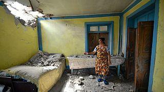 Azerbaycan'ın Tovuz bölgesinde yaşayan bir kadın Ermenistan ordusunun attığı toplardan birinin düştüğü evinin durumunu gösteriyor