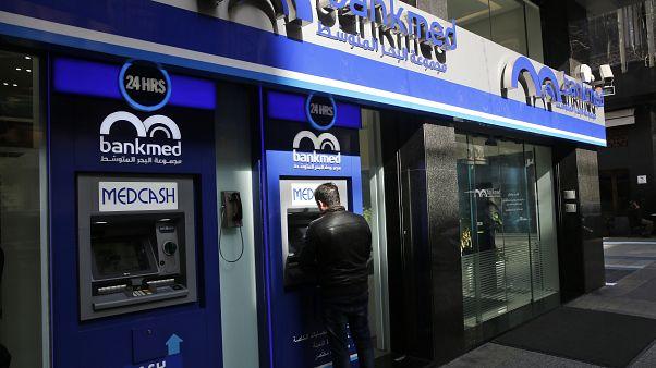رجل لبناني يسحب النقود من ماكينة مصرفية  وسط  بيروت، لبنان