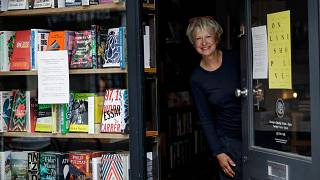 Jane Howe, owner of the Broadway Bookshop, poses for a photo in the doorway of her shop on Broadway Market in Hackney, east London on June 28, 2020