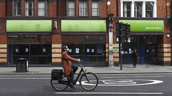 A woman wearing a mask rides a bicycle past a job centre in Shepherd's Bush, London.
