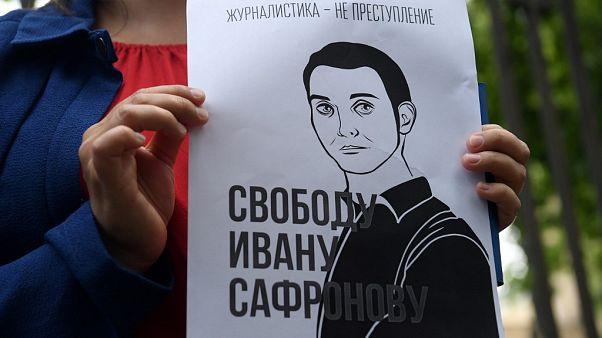 Сторонник Ивана Сафронова держит плакат в его поддержку.