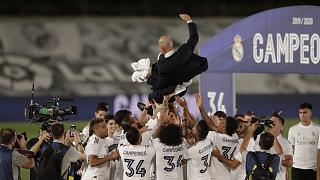 Real Madrid players throw head coach Zinedine Zidane in the air as they celebrate after winning the La Liga title.