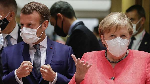 German Chancellor Angela Merkel, right, and French President Emmanuel Macron arrive for a round table meeting at an EU summit in Brussels, Friday, July 17, 2020