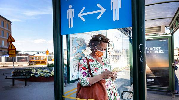 A woman wears a face mask at a bus stop, with an information sign asking people to keep social distance due to the corona pandemic, in Stockholm, Friday, June 26, 2020.