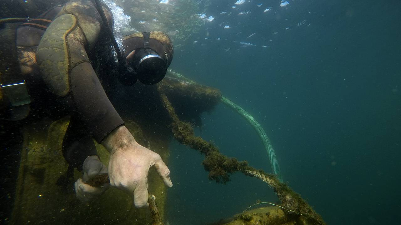 A diver pulls a shipwreck's rope during a raising operation, on Salamina island, west of Athens, on Wednesday, Feb. 13, 2020.