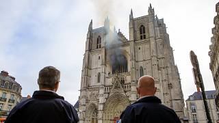 French police officers look at the Gothic St. Peter and St. Paul Cathedral, in Nantes, damaged by a blaze on Saturday morning. July 18, 2020