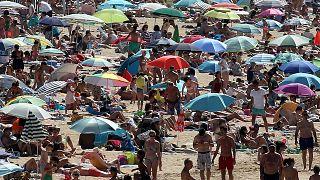 La gente toma el sol en la playa de San Juan de Luz, en el suroeste de Francia, el sábado 18 de julio.