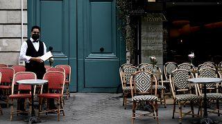 نادل في مطعم فرنسي يضع الكمامة