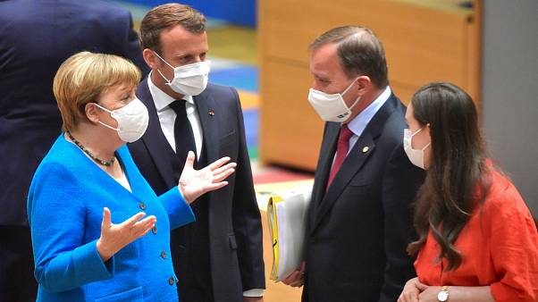 German Chancellor Angela Merkel, left, and French President Emmanuel Macron, second left, speak with Sweden's Prime Minister Stefan Lofven, second right, and Finland's Prime M