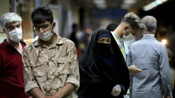 People wearing protective face masks to help prevent the spread of the coronavirus walk in a metro station, in Tehran, Iran