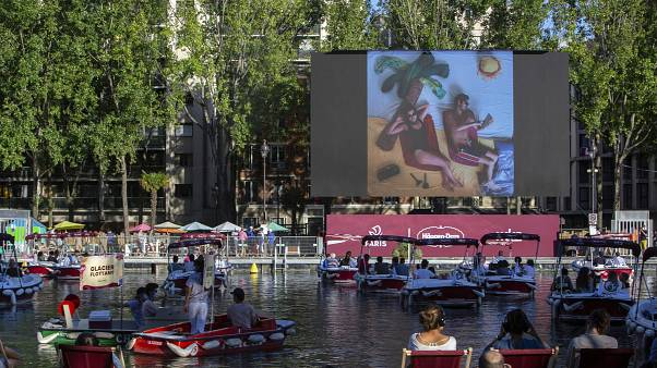 """People on boats attend the """"Le Cinema Sur L'Eau"""", or Cinema on the Water, organized by Paris Plages."""