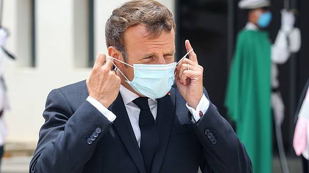 French President Emmanuel Macron puts on a face mask after arriving at Mauritania's Nouakchott--Oumtounsy International Airport on June 30, 2020